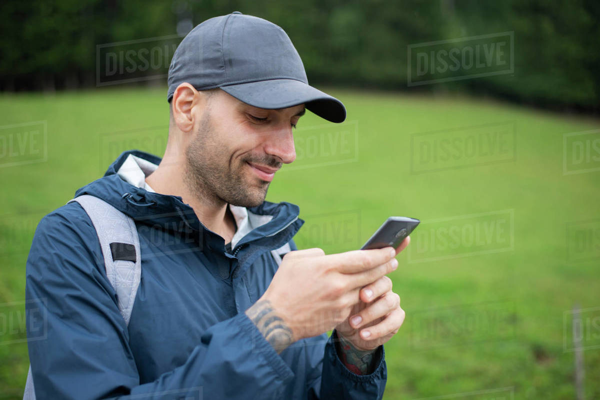 Man using smart phone while standing outdoors Royalty-free stock photo
