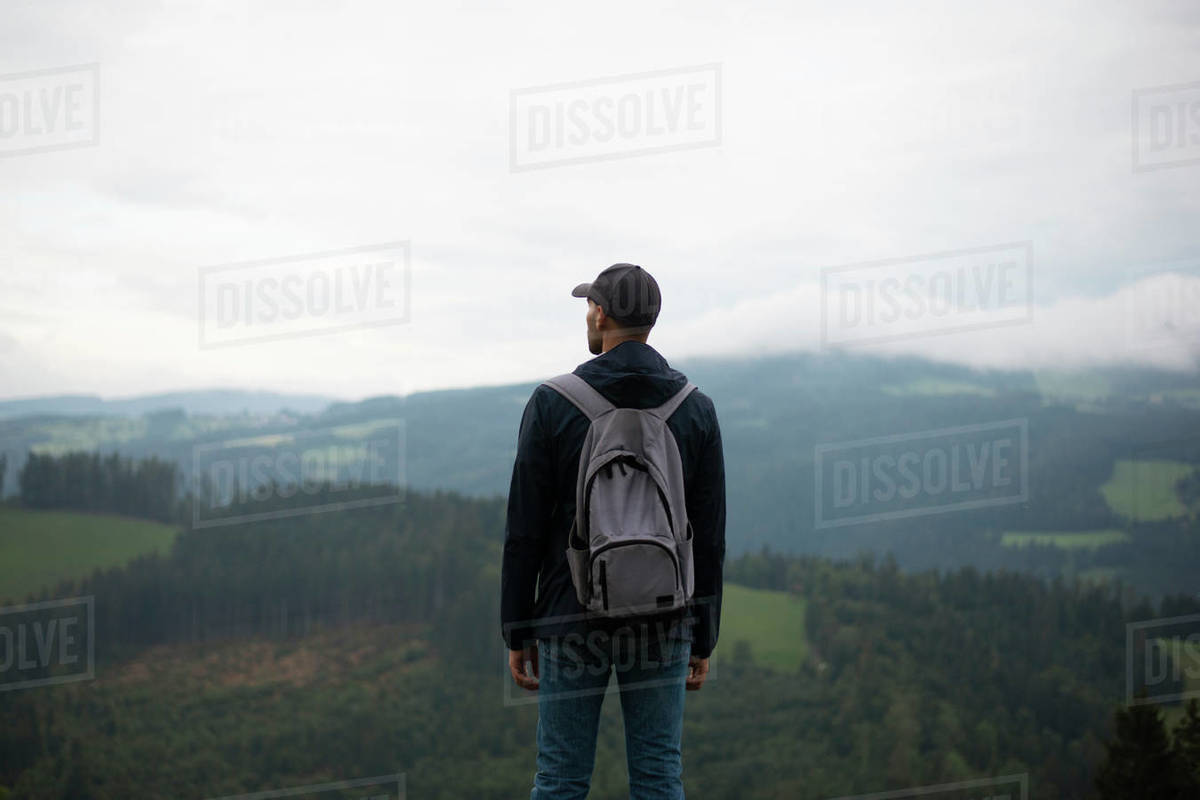 Back view of man with backpack standing and looking at forested mountains from the hill Royalty-free stock photo