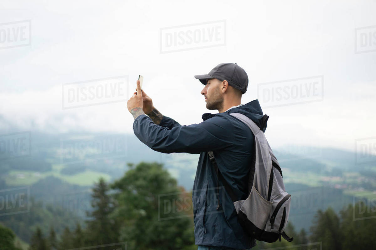 Man photographing by smart phone in forested mountains during foggy weather Royalty-free stock photo