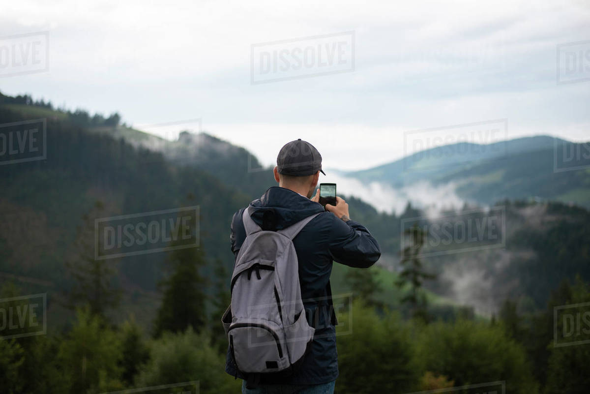 Man photographing mountains through mobile phone Royalty-free stock photo