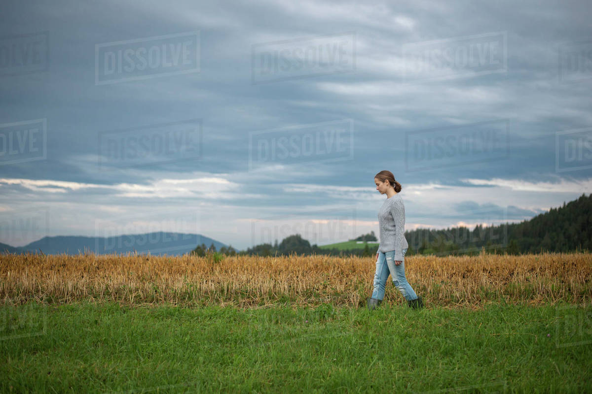 Female farmer walking across remote field in mountains Royalty-free stock photo