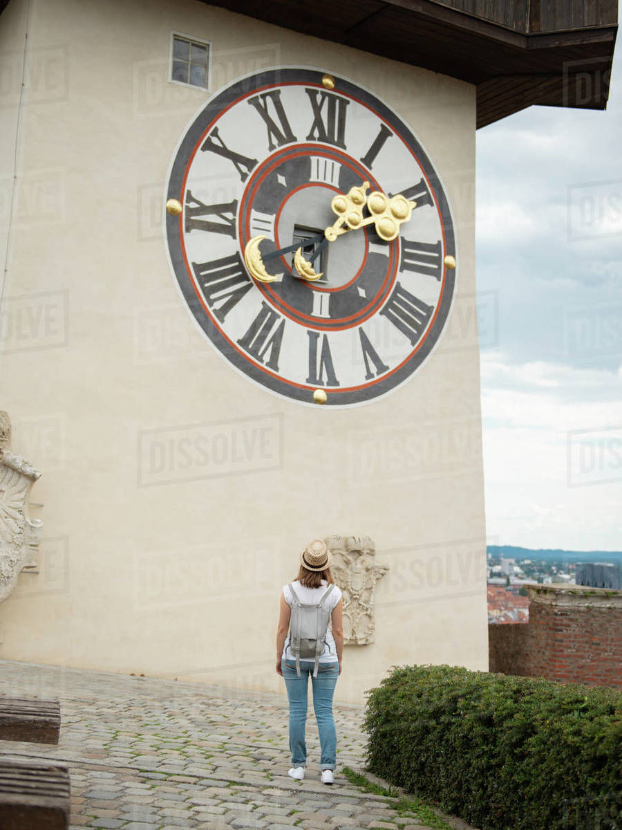 Back view of woman standing and looking at  medieval Clock tower Uhrturm in city Graz, Austria Royalty-free stock photo