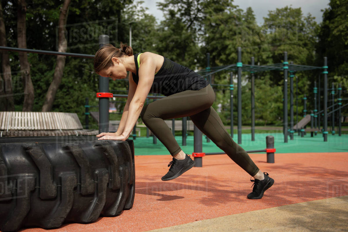Fit female athlete working out with a huge tire outdoors  Royalty-free stock photo