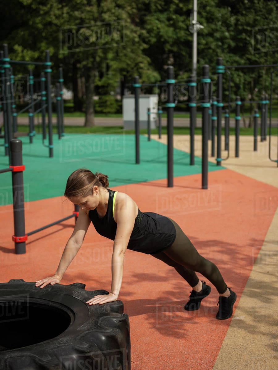 Woman exercising outdoors doing push-ups  Royalty-free stock photo
