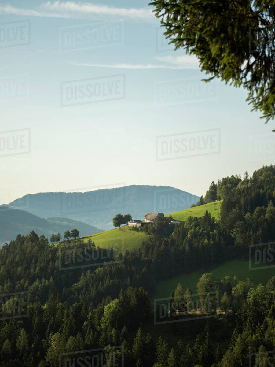 Farmhouse in forested mountains during sunrise Royalty-free stock photo