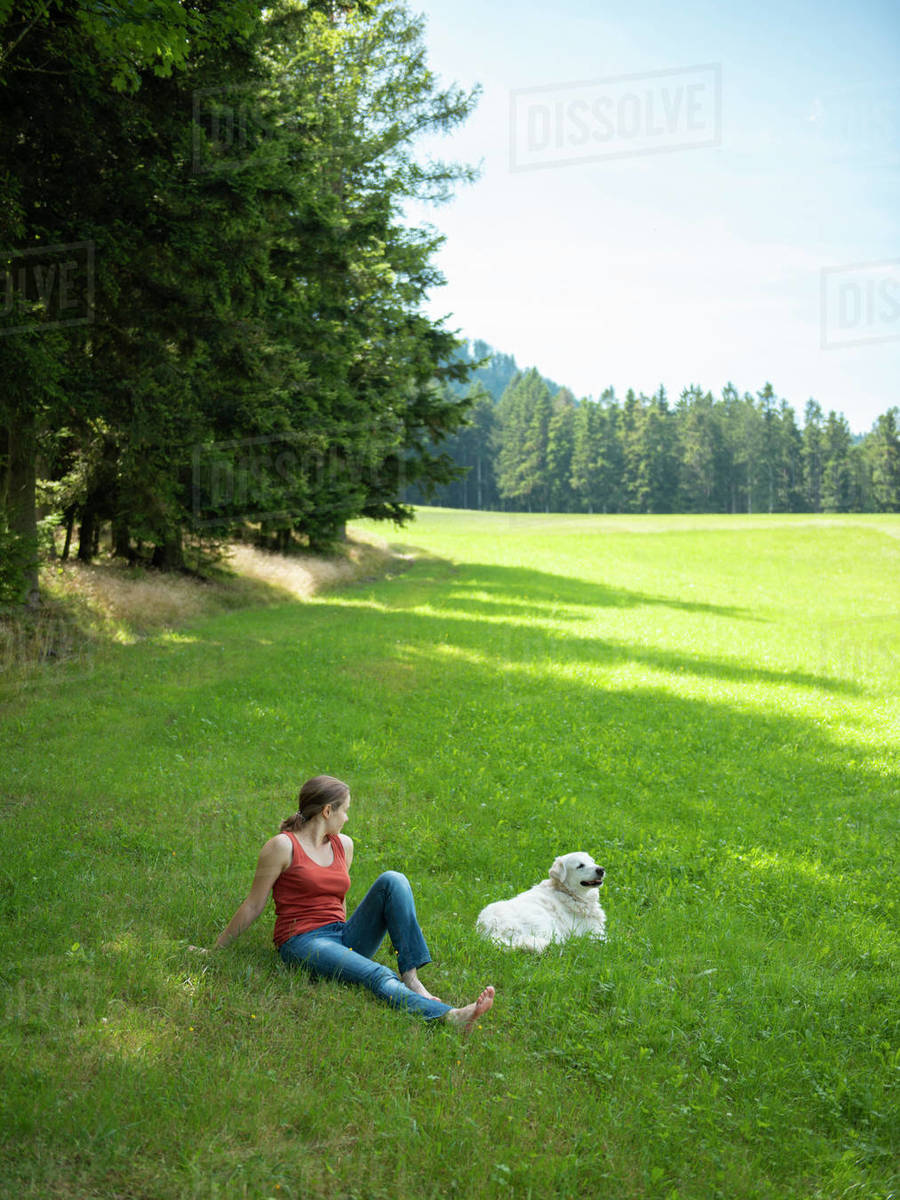 Woman sitting on grass in forest with her dog Royalty-free stock photo