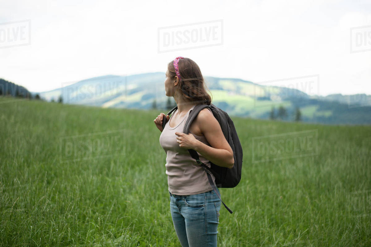 Woman with backpack standing in field looking into distance Royalty-free stock photo