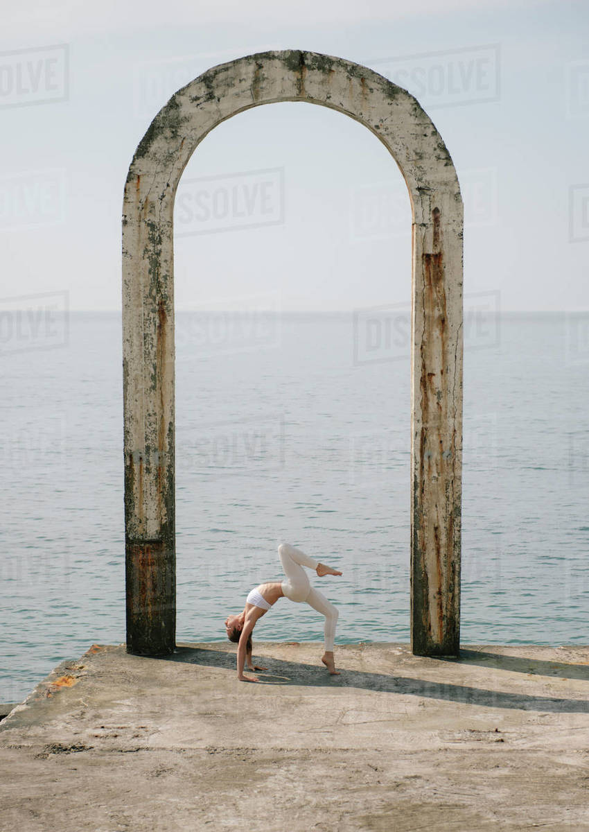 Woman practicing yoga at seaside during sunny day Royalty-free stock photo