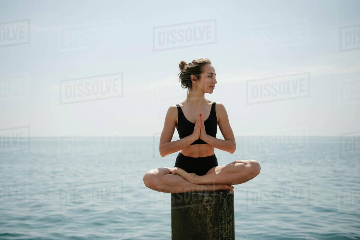 Woman practicing yoga sitting in lotus pose at seaside  Royalty-free stock photo