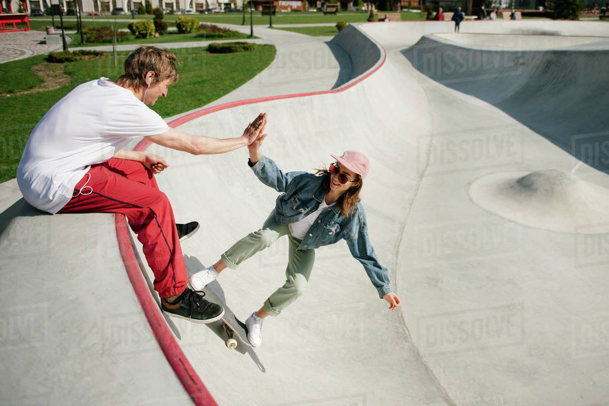 Young smiling woman doing skateboarding trick high fiving her boyfriend Royalty-free stock photo