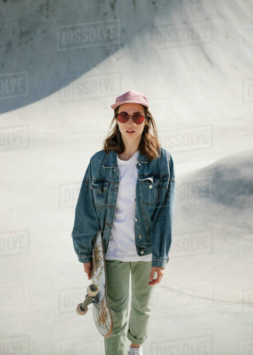 Young woman carrying skateboard looking at camera Royalty-free stock photo