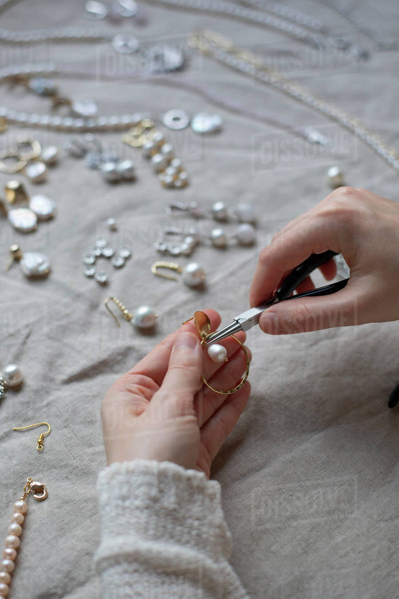 Jewelry designer working in studio with tools making pearl earrings Royalty-free stock photo