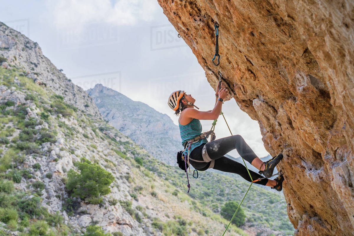 From below side view of active focused youthful female alpinist climbing on cliff in summer day Royalty-free stock photo