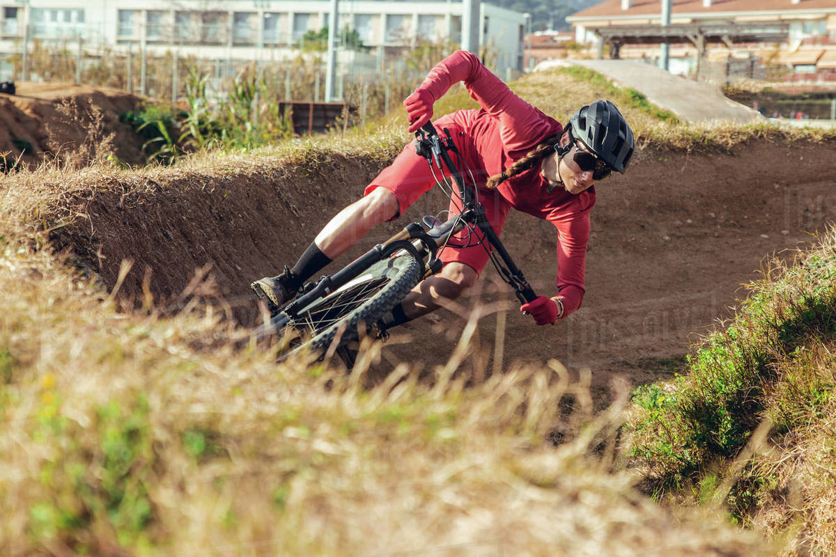 Sportswoman in black helmet and red sportswear with glasses riding mountain bike on training track Royalty-free stock photo