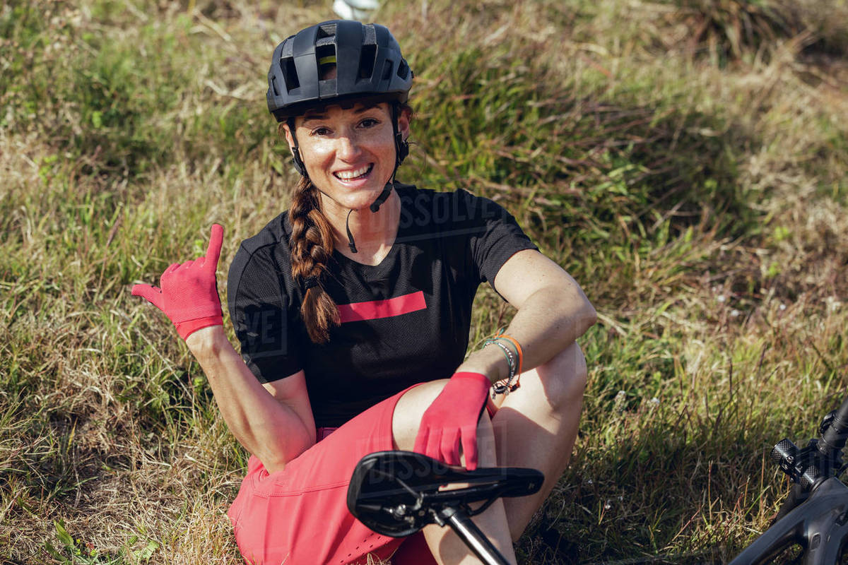Sportswoman in black helmet and red sportswear sitting resting near training track looking at camera Royalty-free stock photo