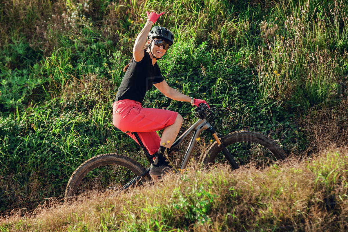 Sportswoman in black helmet and red sportswear with glasses riding mountain bike in training track Royalty-free stock photo