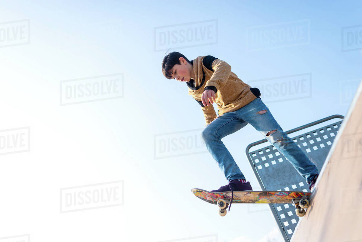 From below teenage boy performing trick on skateboard on ramp while practicing tricks on sunny day Royalty-free stock photo