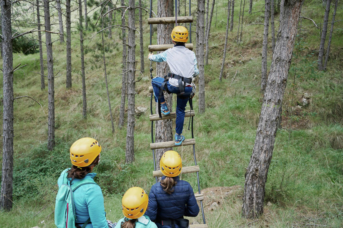 Back view of anonymous woman and girls in helmets watching boy climbing ladder while spending time in adventure park together Royalty-free stock photo