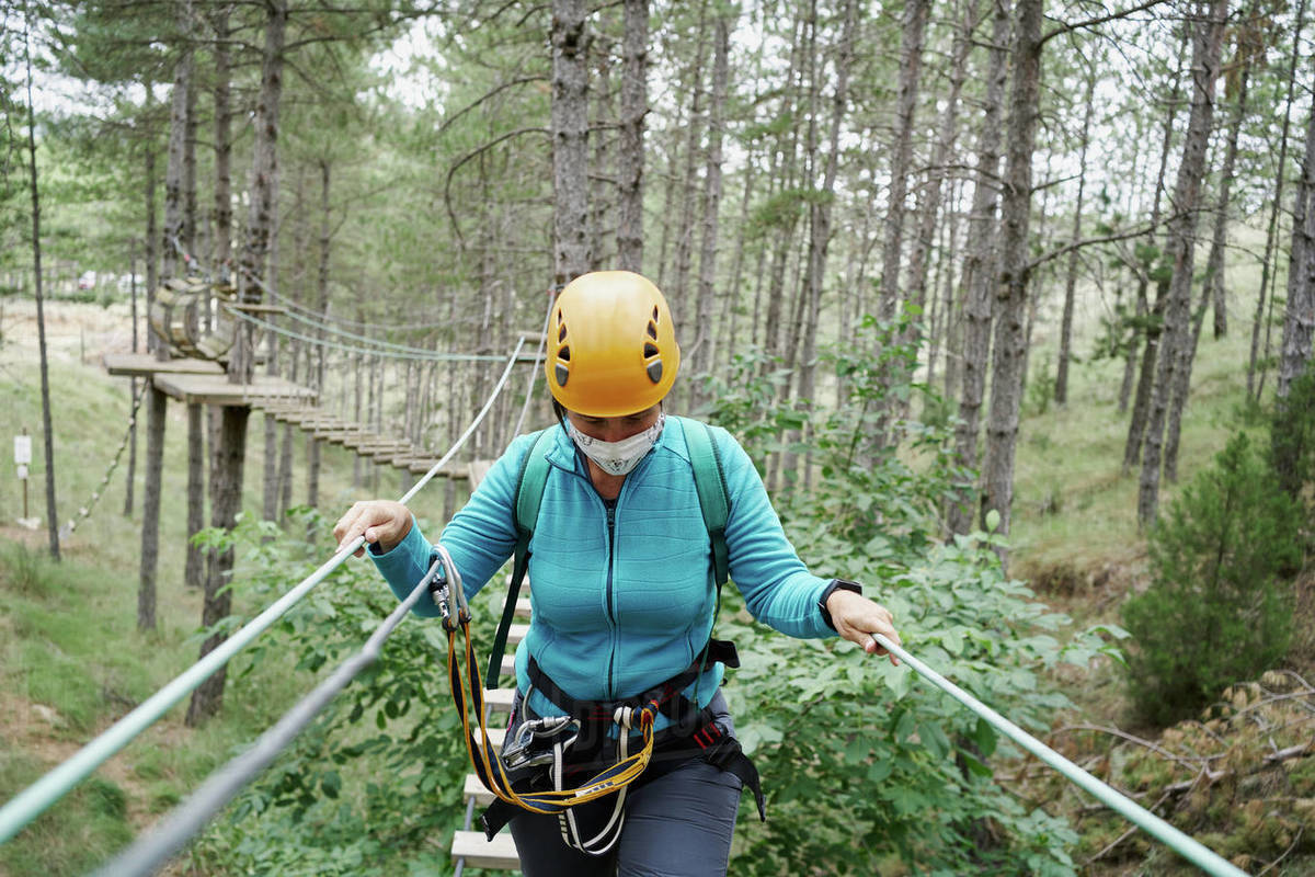 Girl with helmet and safety harness using self belay and walking on hanging path in adventure park in forest Royalty-free stock photo