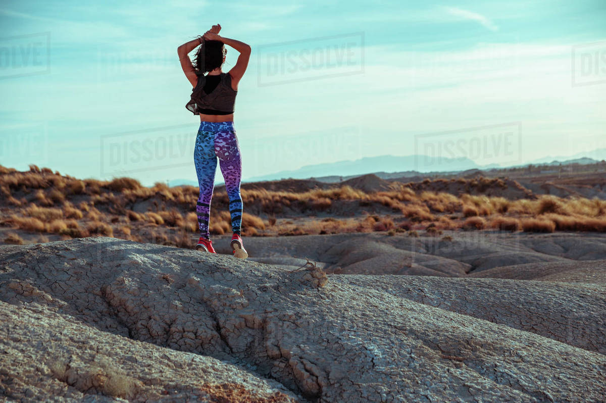 Back view of unrecognizable female in sportswear standing with outstretched arms on rocky hill among desert badlands against blue cloudy sky Royalty-free stock photo
