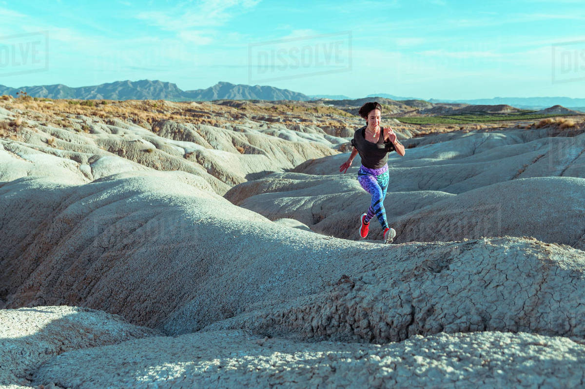 Full body active female athlete in sportswear running and jumping over rocky slope of rough desert hilly terrain under blue sky Royalty-free stock photo