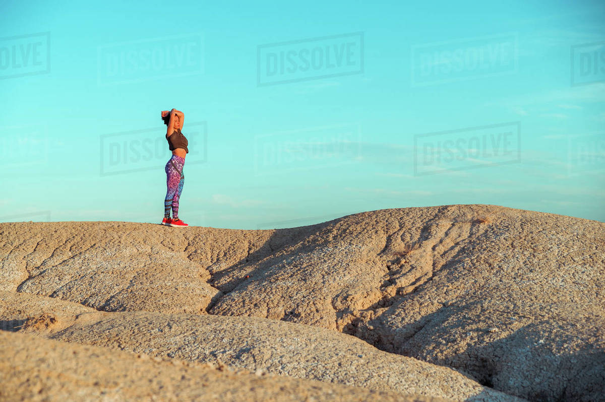 Side view of unrecognizable female in sportswear standing with outstretched arms on rocky hill among desert badlands against blue cloudy sky Royalty-free stock photo