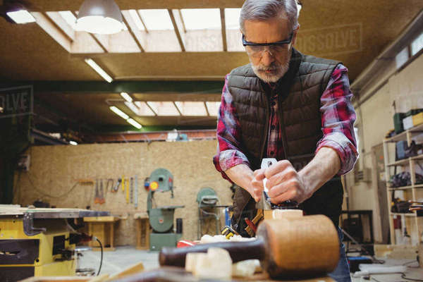 Carpenter using a sander to make smoother a wood plank in his workshop Royalty-free stock photo