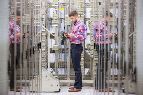 Technician using digital tablet while analyzing server in server room Royalty-free stock photo