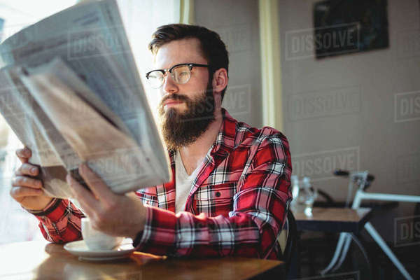 Young customer reading newspaper at coffee house Royalty-free stock photo