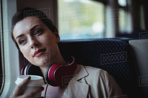 Thoughtful beautiful woman holding disposable cup in train Royalty-free stock photo