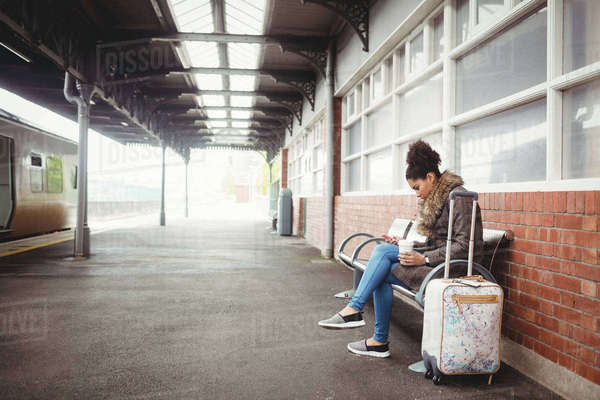 Young woman using phone while sitting at railway station Royalty-free stock photo