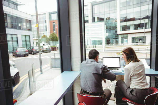 Man and woman discussing over laptop in the cafeteria Royalty-free stock photo