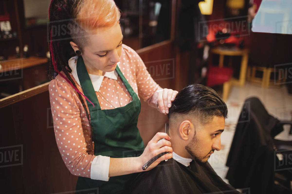 Man Getting His Hair Trimmed With Razor In Barber Shop Stock Photo