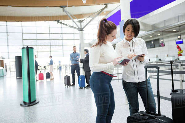 Two womens checking their passport in airport terminal Royalty-free stock photo