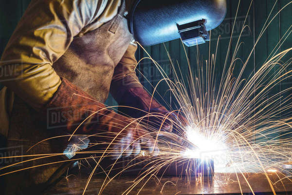 Male welder working on a piece of metal in workshop Royalty-free stock photo