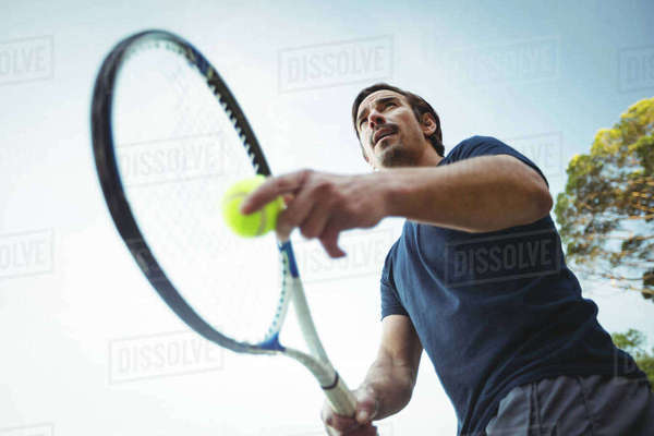 Man with tennis racket ready to serve in the court Royalty-free stock photo