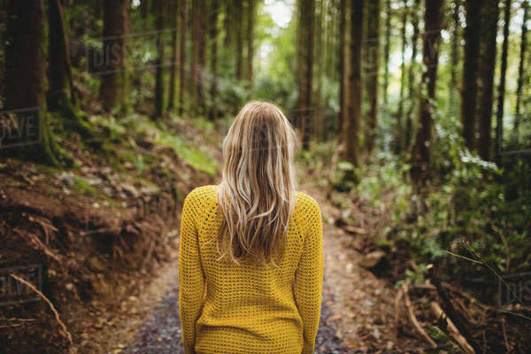 Beautiful blonde woman walking on road surrounded by forest Royalty-free stock photo