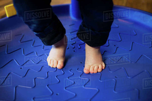 Close up of baby feet in a toy device in the living room Royalty-free stock photo