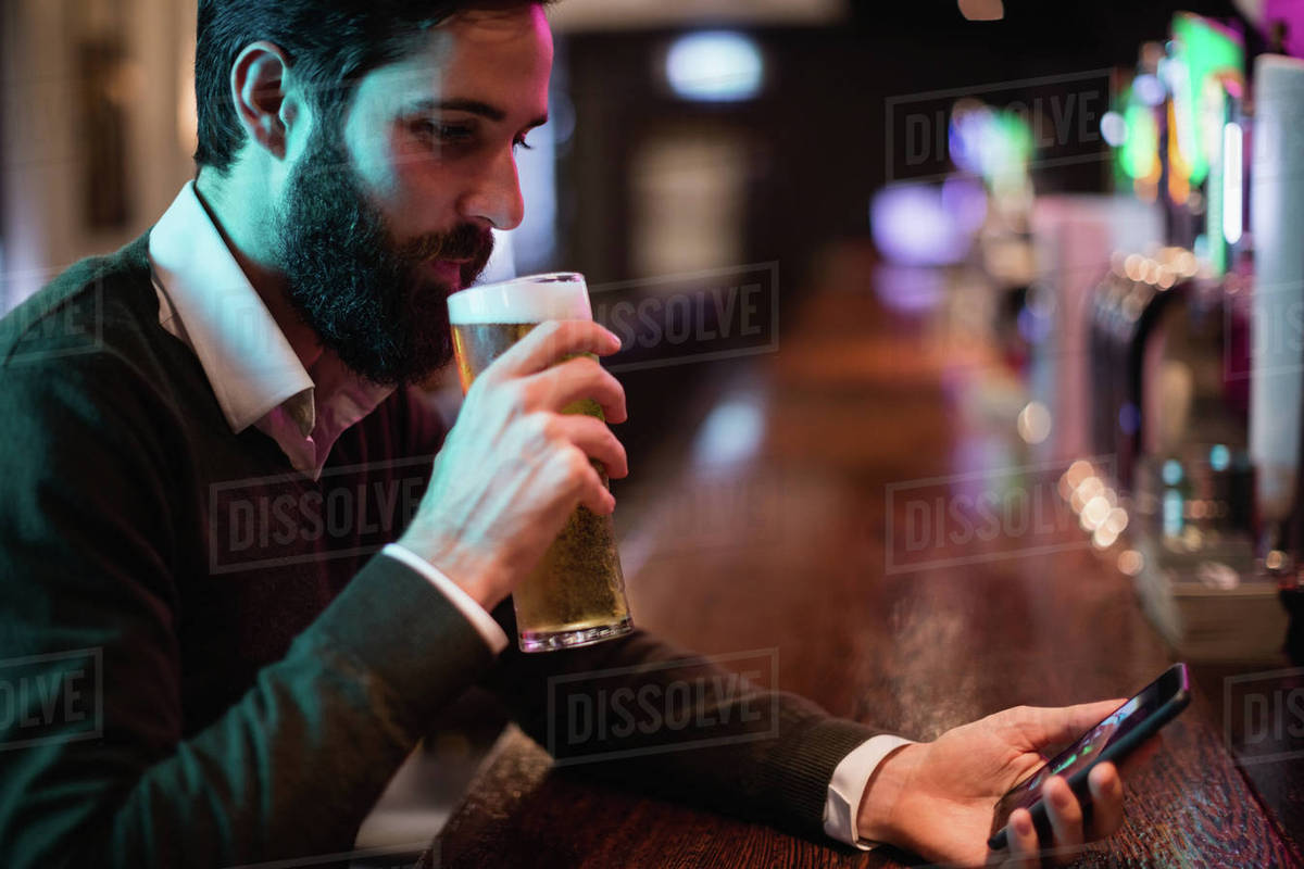 Man looking at mobile phone while having glass of beer in bar ...