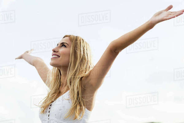 Beautiful blonde woman with arms outstretched in the coastline Royalty-free stock photo