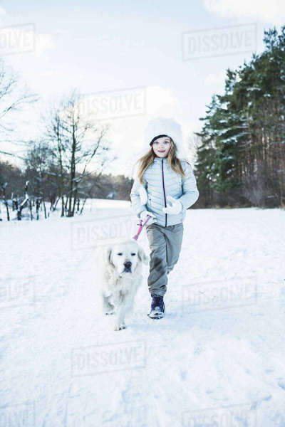 Cute girl walking with dog on a beautiful snowy day Royalty-free stock photo