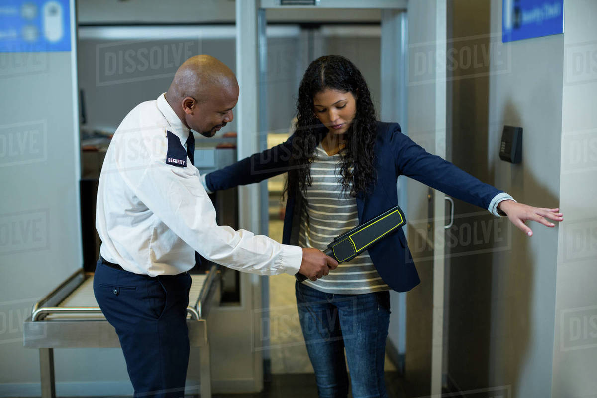 Airport security officer using a hand held metal detector to check a commuter in airport stock - Security guard hd images ...