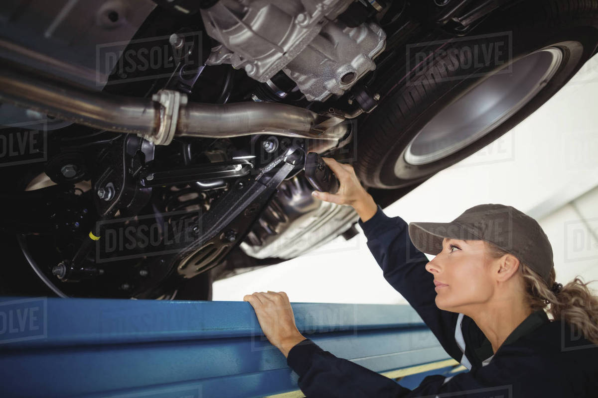 female mechanic examining a car with flashlight in repair garage