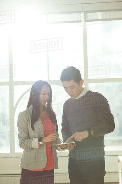 Male and Female executives discussing over digital tablet at office Royalty-free stock photo
