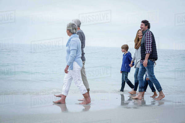 Full length of happy multi-generation family walking at sea shore Royalty-free stock photo