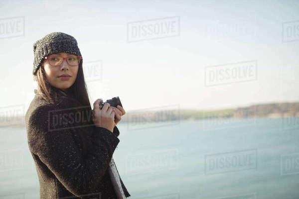 Beautiful woman holding a digital camera near lake in park Royalty-free stock photo