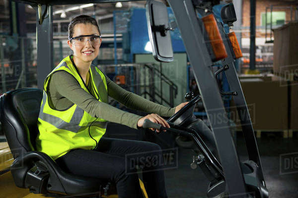 Portrait of beautiful female worker driving forklift in warehouse Royalty-free stock photo
