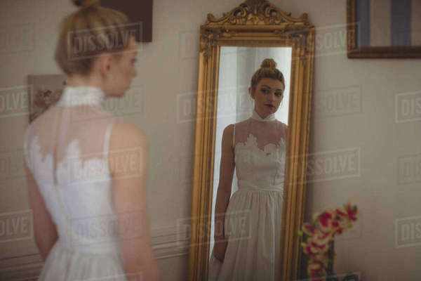 Young bride in a white dress looking into mirror in a boutique Royalty-free stock photo