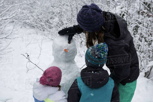 Mother with children making snowman on beautiful snowy day Royalty-free stock photo