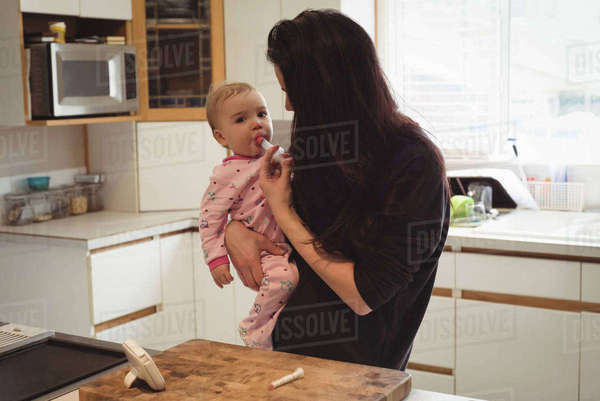 Mother feeding medicine to baby in kitchen at home Royalty-free stock photo